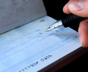 אדם רושם שיק להחזר הלוואה