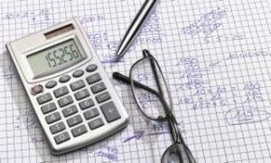 משקפיים, מחברת עם חישובים ומחשבון לצורך חישוב החזר הלוואה