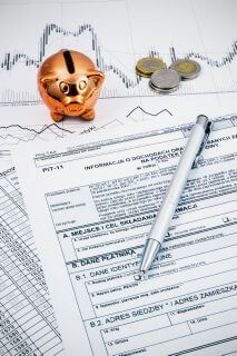Polish income tax forms with pen, coins and piggybank