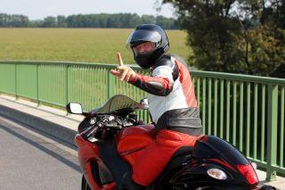 Mann auf Motorrad zeigt Finger