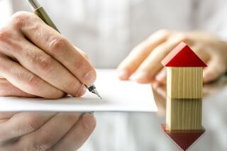 Man signing a contract when buying a new house